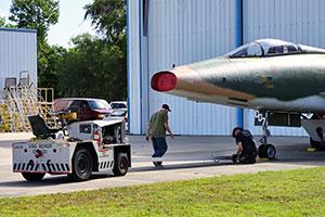 Museum volunteers help move a warbird