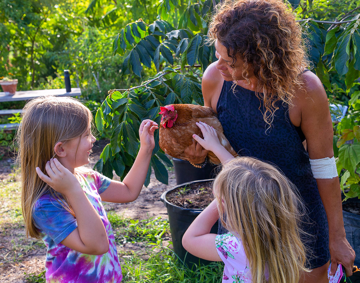 Marks-Monge holds one of the yard's resident chickens