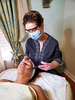 Corina Gata performs a microcurrent treatment on client Kim O'Grad
